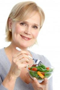 picture of woman eating vegetables