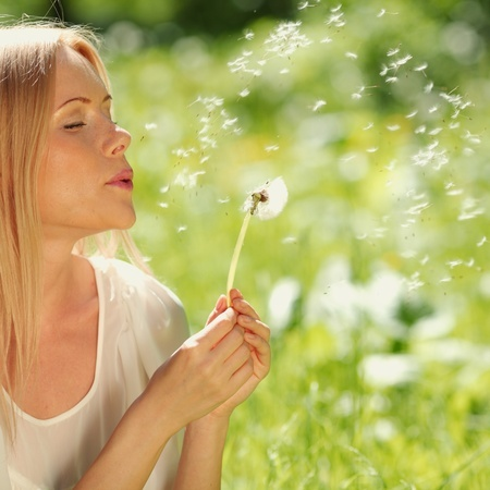 Image of woman blowing dandelion