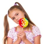 Girl holding a lollipop with artificial food colors